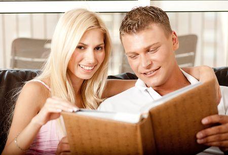 Lady and guy going through album and cherishing past days Standard-Bild