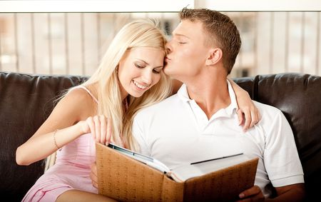 Lady going through album and cherishing past days as man kisses her on forehead