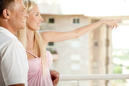 Young couple smiling in balcony as woman points out something