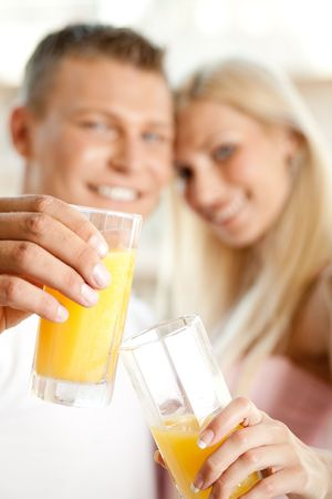 Couple holding juice glass and looking at camera Standard-Bild