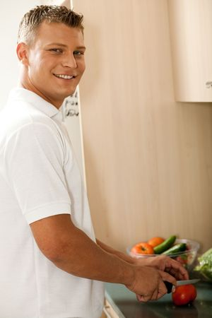 Young man cutting vegetable and preparing the base for dinner