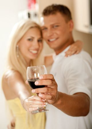 Smiling young couple sharing wine glass in kitchen and facing camera