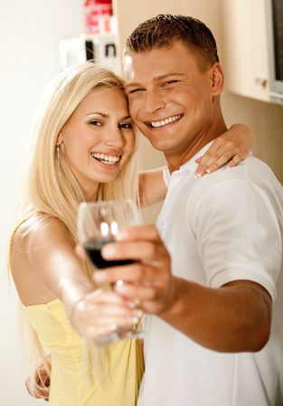 Couple sharing wine glass and smiling as they look into the camera