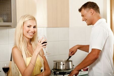 Young male cooking food while his wife enjoys wine