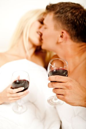 Couple holding wine glass and kissing