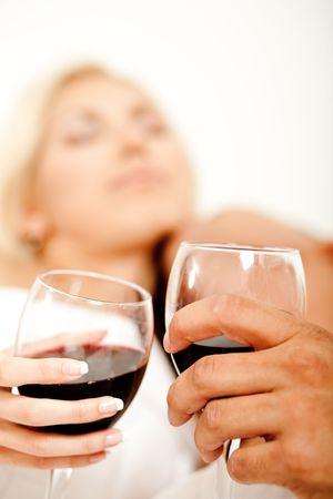 making love: Vaso de vino en el enfoque con pareja haciendo el amor en el fondo Foto de archivo