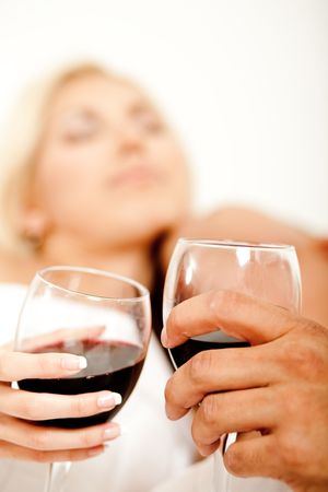 Wine glass in focus with couple making love in background