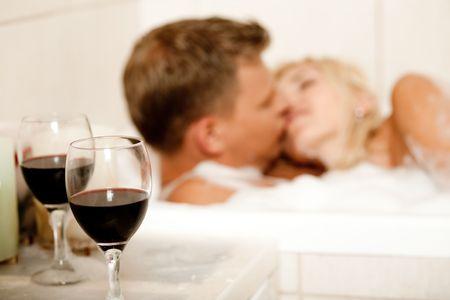 Guy y los besos de la mujer en segundo plano con copa de vino en el enfoque Foto de archivo