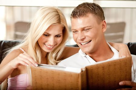 Smiling young couple sharing album together