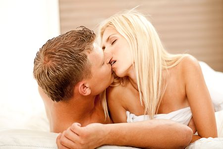 Intimate lovers in bed kissing each other