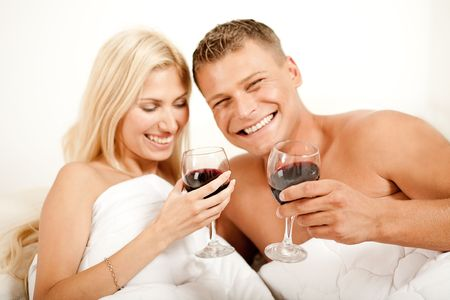 Couple lying in bed together sharing wine and smiling looking at camera Stock Photo - 5746362