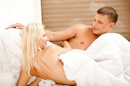 Nude lovers in bed facing each other and smiling photo