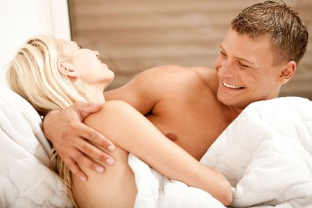 Man and woman having fun in bed and smiling photo