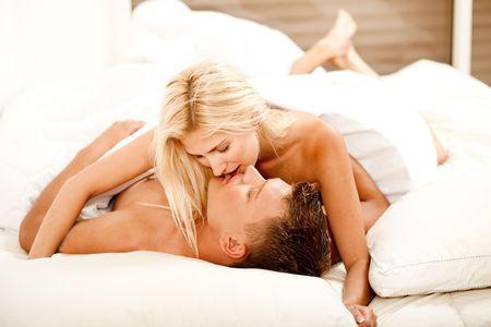 El hombre y la mujer se besan y hacen el amor en la cama Foto de archivo - 5674031