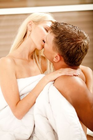 Young couple making love and kissing in bedroom
