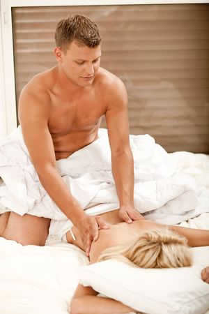 Pretty woman getting massage from handsome young male photo