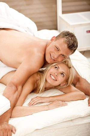 Young sexy couple in bed smiling at camera photo