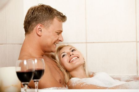 foreplay: Smiling young couple in bath