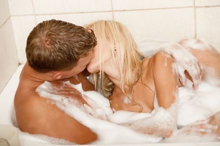 Man and woman kissing in bubble bath photo