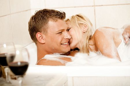 couple bathroom: Pretty female kissing man on his right cheek and smiling Stock Photo