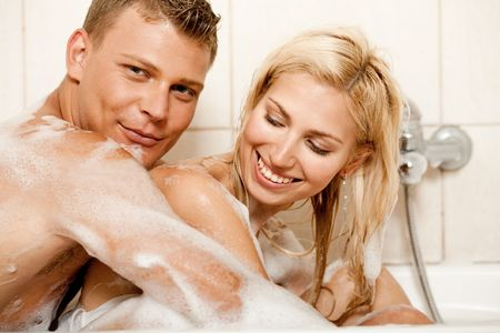 Young man and woman sharing bath and smiling looking at camera photo