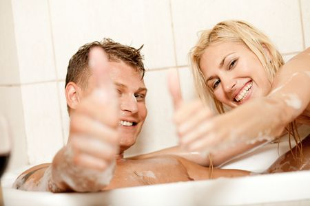 Smiling young couple showing thumbs up photo