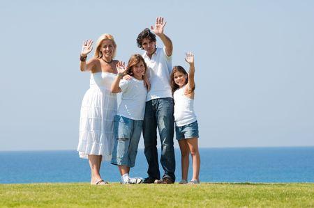 Family of four waving at camera