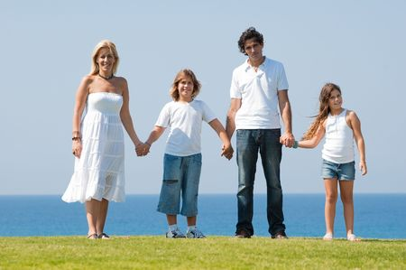 Family on meadow holding hands and looking at camera Standard-Bild