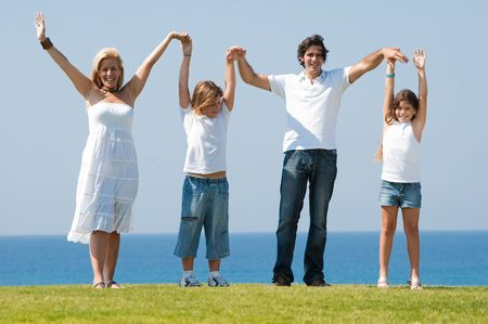 Portarait of happy family of four holidng hands