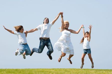 jumping: Happy family salto alto contra el ambiente natural Foto de archivo