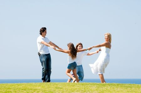 Happy family smiling and enjoying on meadow, outdoors photo