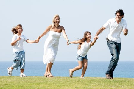 Man and woman running on meadow holding children hands and enjoying photo
