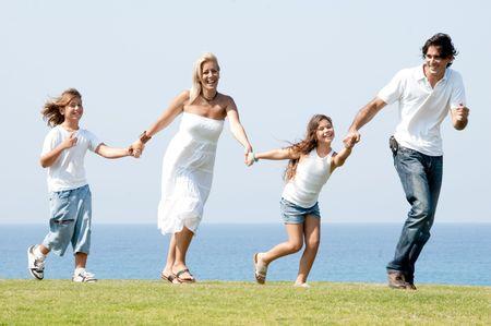 Man and woman running on meadow holding children hands and enjoying Standard-Bild