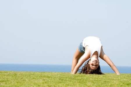 Pretty girl making gymnastic moves on grass Standard-Bild