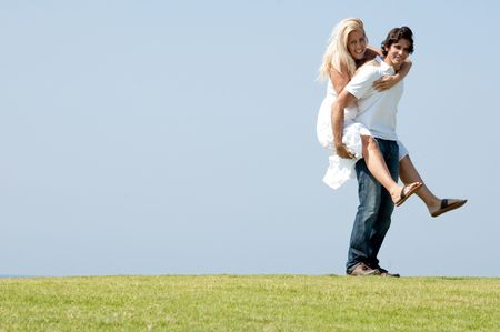 Young man giving piggy ride to woman and smiling Standard-Bild