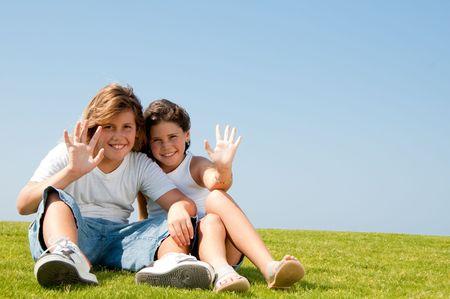 Young kids waving hands at camera and smiling photo
