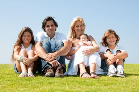 Adorable family sitting on grass and smiling at camera photo