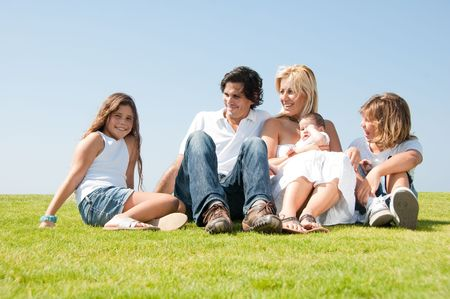 Smiling family relaxing on grass