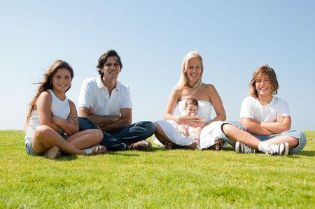 Family enjoying beautiful day, relaxing on meadow Standard-Bild