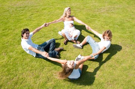 Family enjoying together on grass holding hands, forming circle Standard-Bild