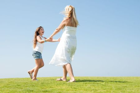 Young girl playing on meadow with her mum photo
