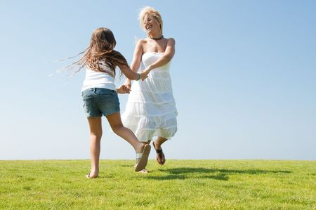 Young mother enjoying with her daughter and playing on meadow Standard-Bild