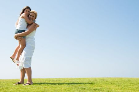 Pretty young girl being held by her mother outdoors, smiling Standard-Bild