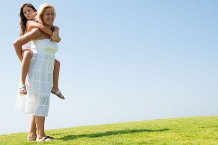 Smiling young woman giving girl piggyback ride and looking at camera