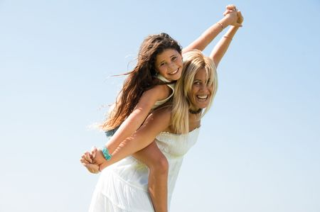 Beautiful woman carrying young girl on her back, smiling and enjoying