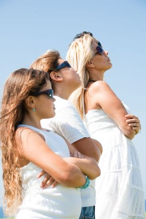 Family of four with goggles on looking at sky