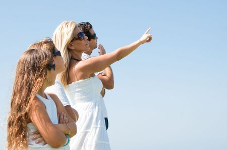 Woman pointing towards sky as family looks up photo