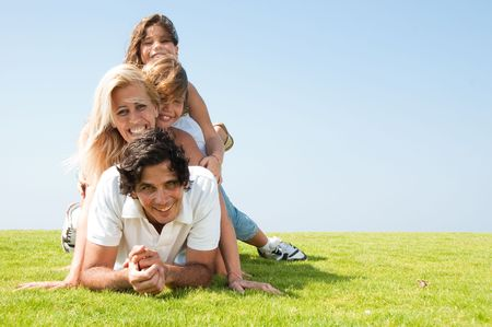 Family piled up on meadow and smiling at camera