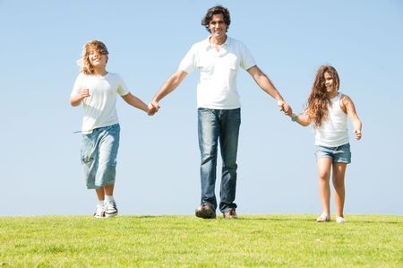 Daddy having fun with his children on meadow as he walks holding their hands