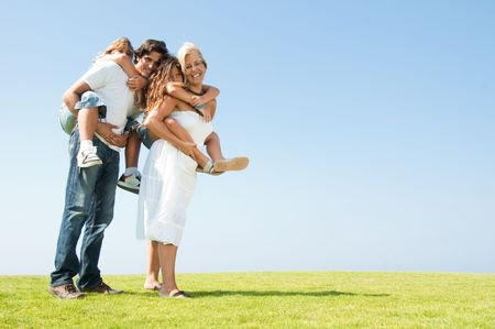 Couple giving two young children piggyback rides on natural background photo